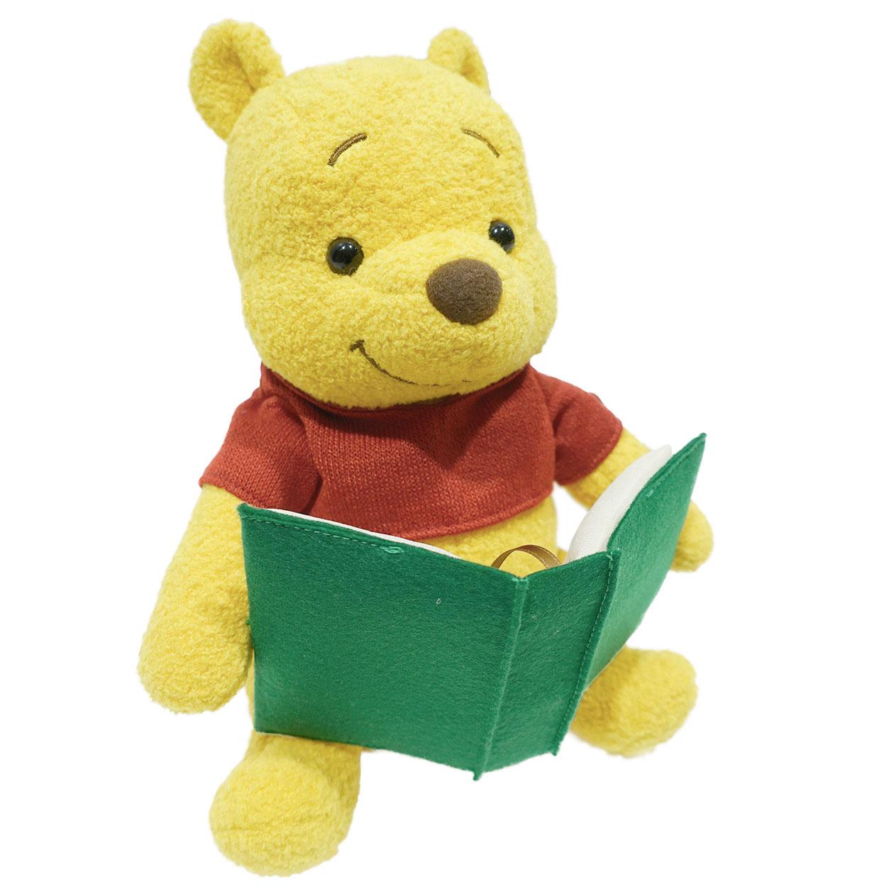 緑色の本を両手で持ったくまのプーさんぬいぐるみ